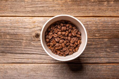 Coffee grains in a paper cup on wooden background. Stock Photo