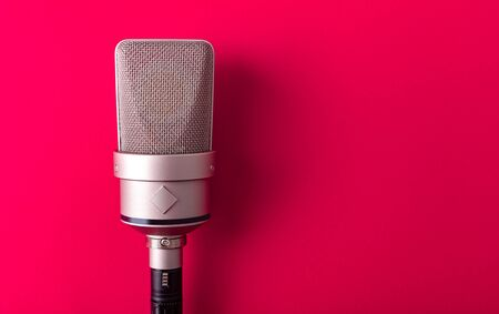 Large diaphragm condenser studio microphone. On red background. Stock Photo