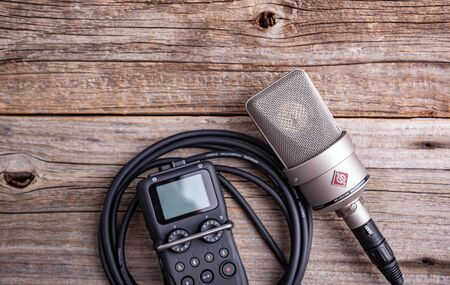Large diaphragm condenser studio microphone Neumann tlm 103 and Zoom H5 recorder on a wooden background.