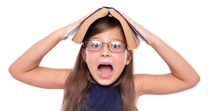 Little girl with an open book on her head is angry.