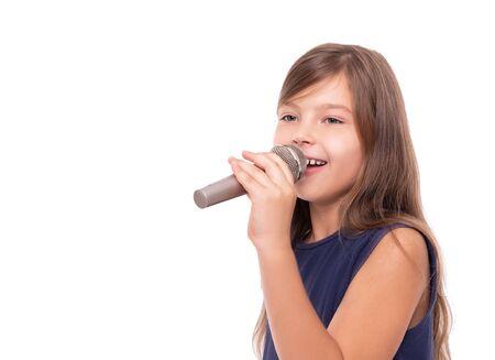 Petite fille posant avec un microphone pour chanter sur fond blanc. Banque d'images