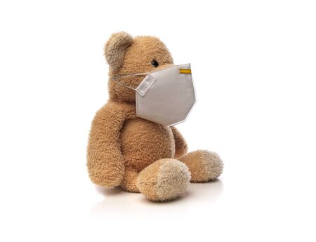 Teddy bear with protective medical face mask on white. Stock fotó