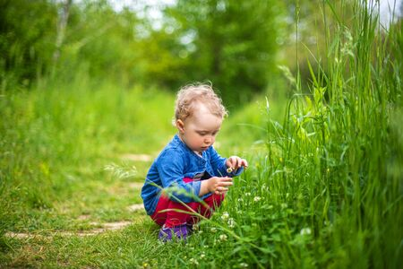 Little girl plays on nature against the background of greenery.