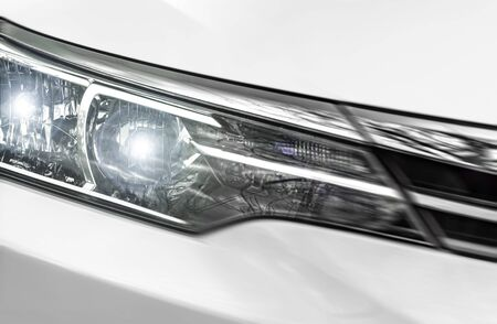 The headlight of the white car is close-up.