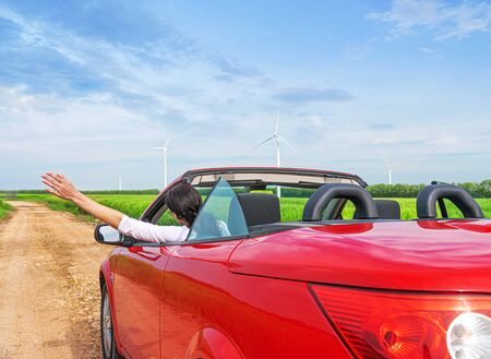 A woman raises her hands in a car in nature. Banco de Imagens