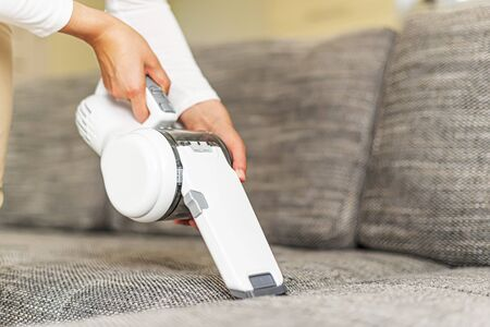 Woman vacuuming furniture in a house with a hand-held portable vacuum cleaner.