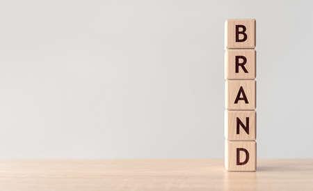 Brand word written on wood block on wooden background.