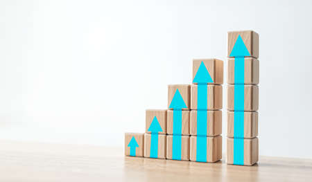 Wood block stacking as step stair with blue arrow up.