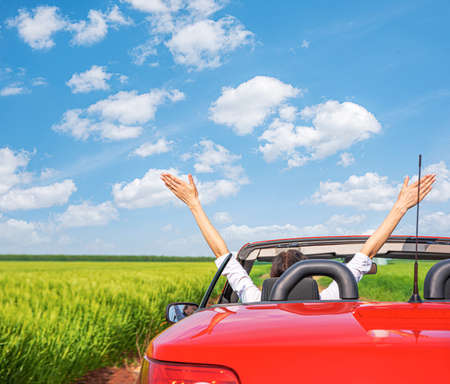 Woman in a red car against the background of a field outside the city.