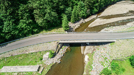 Automobile bridge over the river on the background of the forest in the mountains. Zdjęcie Seryjne