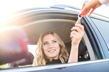 Beautiful woman gets the key from the car