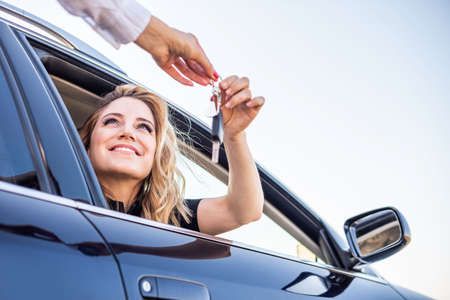 Beautiful woman gets the key from the car Imagens