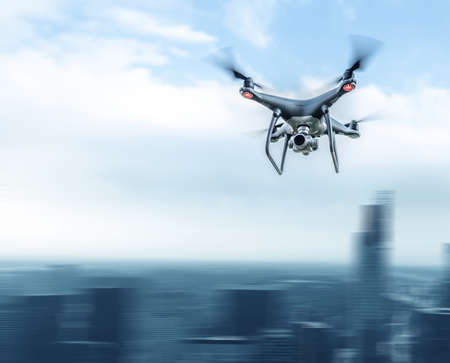 A modern drone in the sky over a large city. Stock Photo