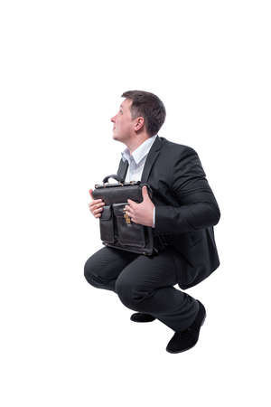 Businessman in a suit with a briefcase in his hands crouched down isolated on white background.