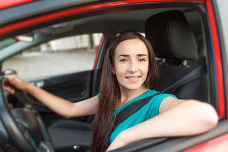 Happy beautiful woman is driving a car. Stock Photo
