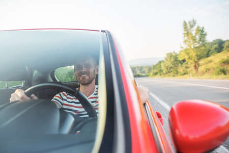 Man with a beard driving a car. Imagens