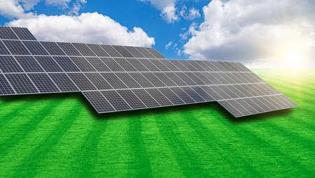 Solar power plant on a green field against the blue sky.
