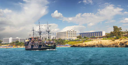 Sailing ship on the background of the beaches of Agia NAPA on a sunny day. Stock Photo