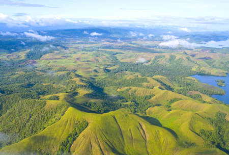Aerial photo of the  coast of New Guinea with jungles and deforestation  Stock Photo