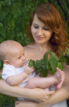 beautiful mother with a baby in a garden photo