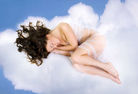 beautiful young woman lying on  clouds photo