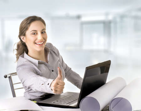young business woman at office with laptop giving thumbs-up-sign