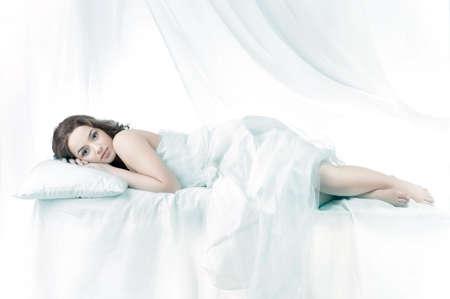 one sheet: Bella donna dorme sopra uno sfondo bianco