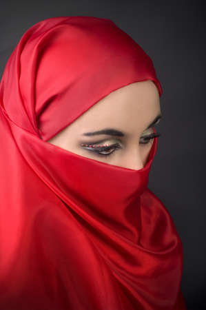 Portrait of a young   arabian girl in red veil  photo