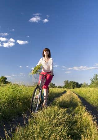 woman riding bike through a field  photo