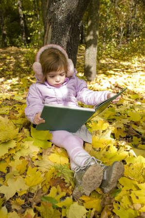girl reads a book in an autumn park photo