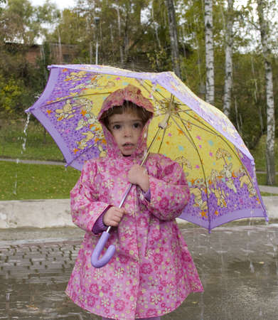 girl with an umbrella in the rain Фото со стока