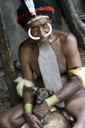 sektor: NEW GUINEA, INDONESIA -DECEMBER 28: The man of a Papuan tribe in traditional clothes and coloring in New Guinea Island, Indonesia on December 28, 2010