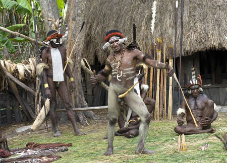 inhabitants: NEW GUINEA, INDONESIA -DECEMBER 28: Unidentified warriors of a Papuan tribe in traditional clothes and coloring in New Guinea Island, Indonesia on December 28, 2010