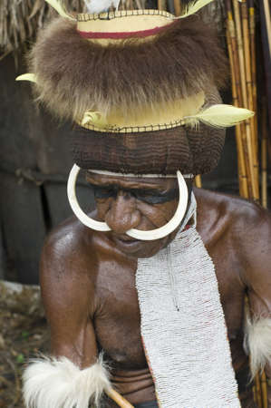 NEW GUINEA, INDONESIA -DECEMBER 28: Unidentified warrior of a Papuan tribe in traditional clothes and coloring in New Guinea Island, Indonesia on December 28, 2010