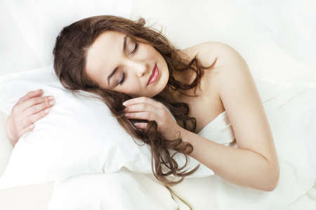 Portrait of the beautiful young woman sleeping in white bed  photo
