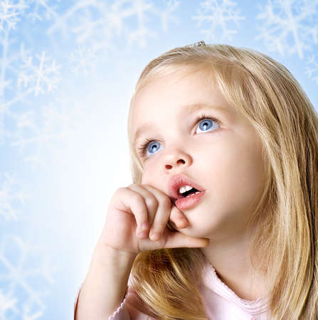 little girl smiling: beauty baby face with blue eyes on blue background with snowflakes Stock Photo