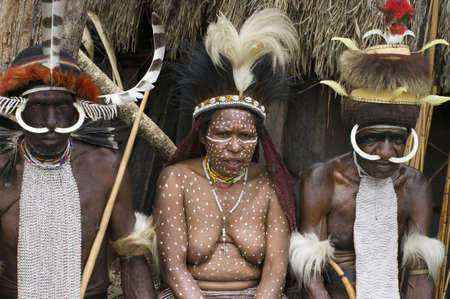 NEW GUINEA, INDONESIA -DECEMBER 28: Unidentified warriors of a Papuan tribe in traditional clothes and coloring sit in front of their home in New Guinea Island, Indonesia on December 28, 2010.