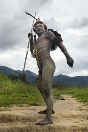 sektor: NEW GUINEA, INDONESIA -DECEMBER 28: Unidentified warrior of a Papuan tribe in traditional clothes is having a demonstration of war skills in New Guinea Island, Indonesia on December 28, 2010