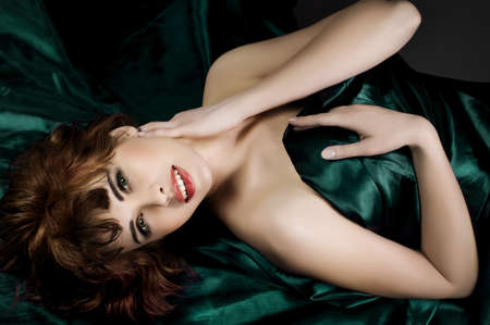 beautiful young woman red hair lying on dark green silk  Stock Photo - 12409238