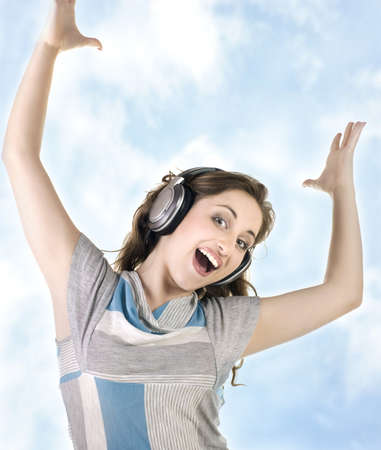 young  girl listening to music on headphones on  sky background photo