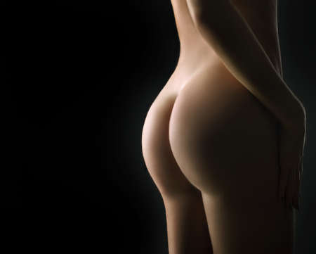 Beautiful ass of young woman over dark background  Stock Photo - 12409199