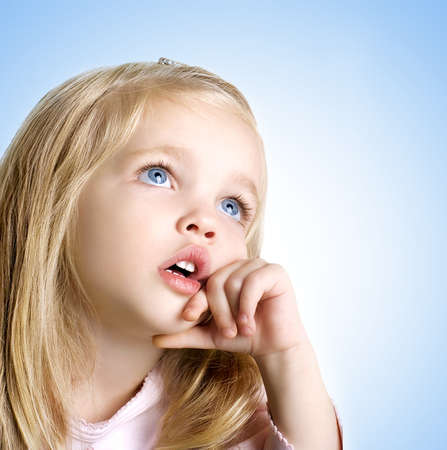 little girl smiling: closeup image of a dreaming beautiful little girl with blue eyes Stock Photo