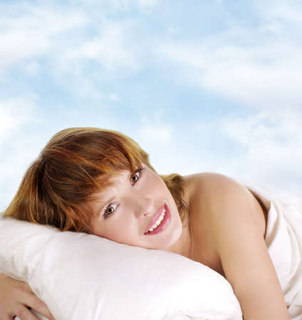 Portrait of the beautiful young sexy woman sleeping in white bed on sky background  photo