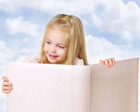 homestudy: Portrait of a little girl reading  a book on sky background