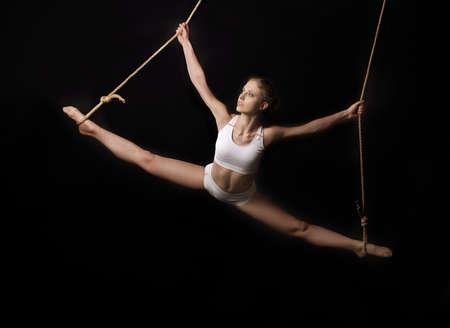 acrobacia: Gimnasta joven, mujer, sobre fondo negro Foto de archivo