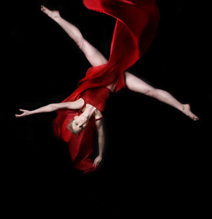 trapeze: Young woman gymnast wearing red dress on rope on black background