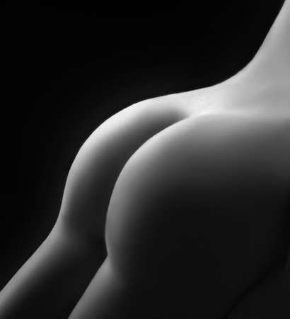 nude butt: Beautiful ass of young woman over dark background, white   black