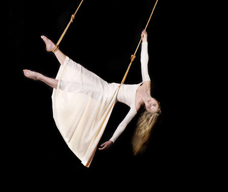 Young woman gymnast in white dress on rope on black background Stock Photo - 13443987