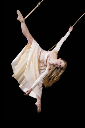 Young woman gymnast in white dress on rope on black background Stock Photo - 13443986