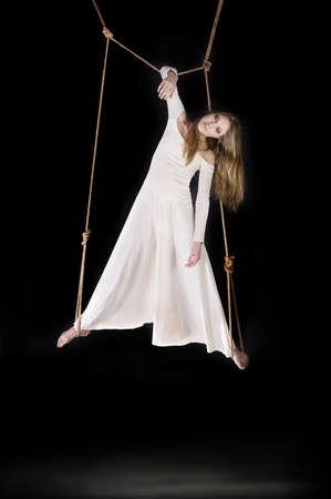 titeres: Gimnasta joven, mujer, vestido de blanco en la cuerda sobre fondo negro Foto de archivo